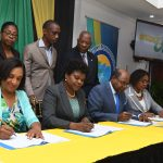 Minister of Tourism, Hon. Edmund Bartlett (seated, second-right) signs a memorandum of understanding with the Edna Manley College of the Visual and Performing Arts to establish a Craft Development Institute (CDI) in St. Ann's Bay. Also participating in the signing ceremony are (seated from left) Acting Executive Director of the Tourism Product Development Company, Joy Roberts; Permanent Secretary in the Ministry of Tourism, Jennifer Griffith and Principal of the Edna Manley College of the Visual and Performing Arts, Dr. Nicholeen DeGrasse-Johnson. Sharing in the moment are (standing from left), Senior Director of the Planning and Development Division in the Ministry of Youth, Education and Information, Barbara Allen; the Jamaica Hotel and Tourist Association's Chapter Chairman for Kingston, Christopher Jarrett; and Chairman of the Tourism Enhancement Fund, Godfrey Dyer. The MOU signing took place during the press launch of the revamped Spruce Up Jamaica programme on January 24, 2017 at the iconic Devon House in Kingston. The CDI, which is a major Spruce Up Jamaica initiative, is scheduled to welcome the first students in the September 2018.