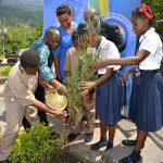 Member of Parliament for West Rural St. Andrew, Juliet Cuthbert Flynn (centre) looks on as Students of the Lawrence Tavern Primary School participate in a tree planting exercise. She is joined by (from left) Councillor for the Lawrence Tavern division, John Myers and Director of Product Development and Community Tourism, TPDCo, Julian Patrick. The occasion was the launch of the Trash to Treasure School Environmental Competition which seeks to encourage safer environmental practices among Primary level students.